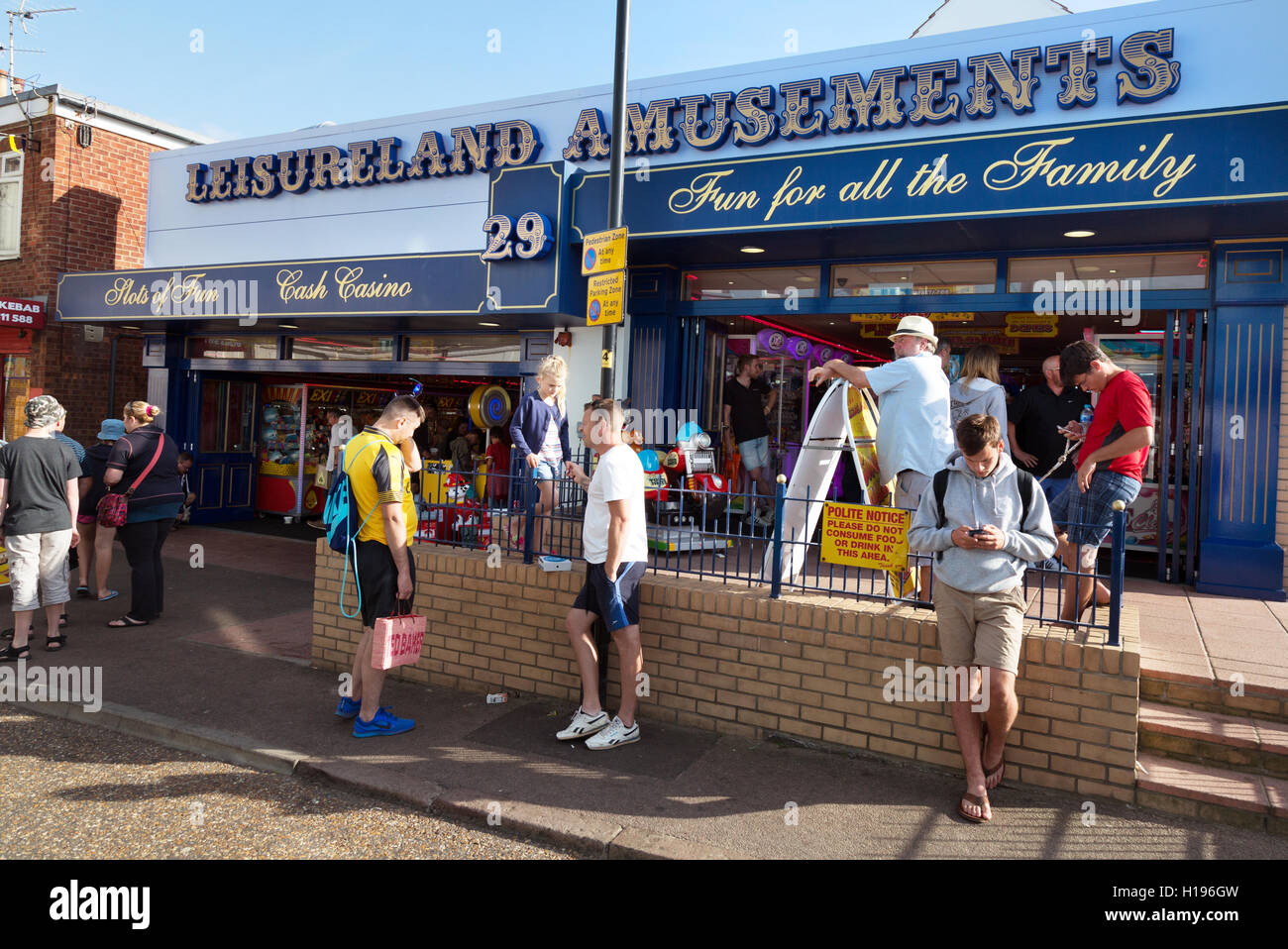 People outside an musements arcade on a sunny summers day, Cromer, North Norfolk coast, Norfolk England UK - Stock Image