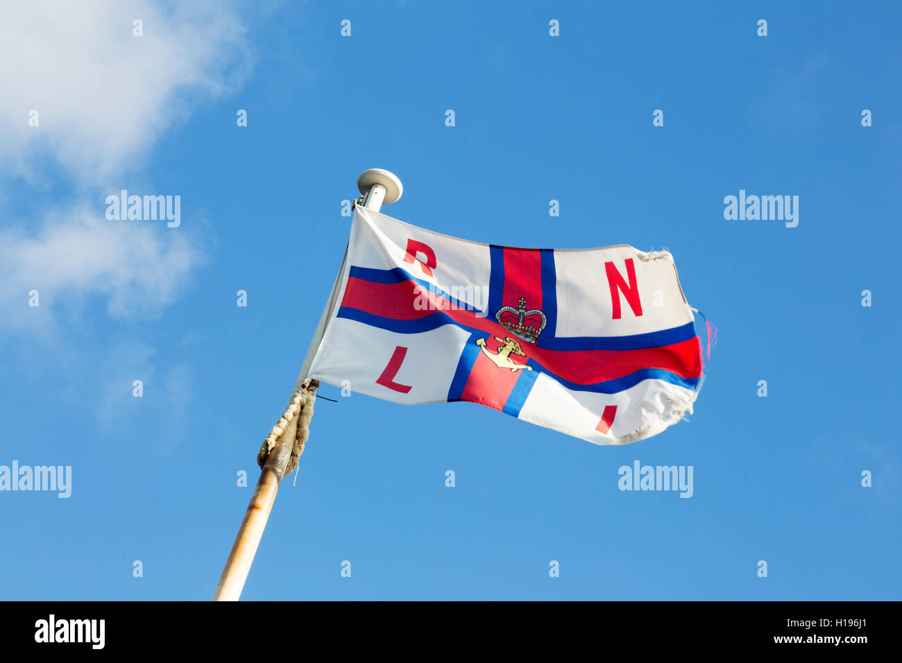 RNLI  ( Royal National Lifeboat Institution ) flag flying on a flagpole against a blue sky,  Norfolk, UK - Stock Image