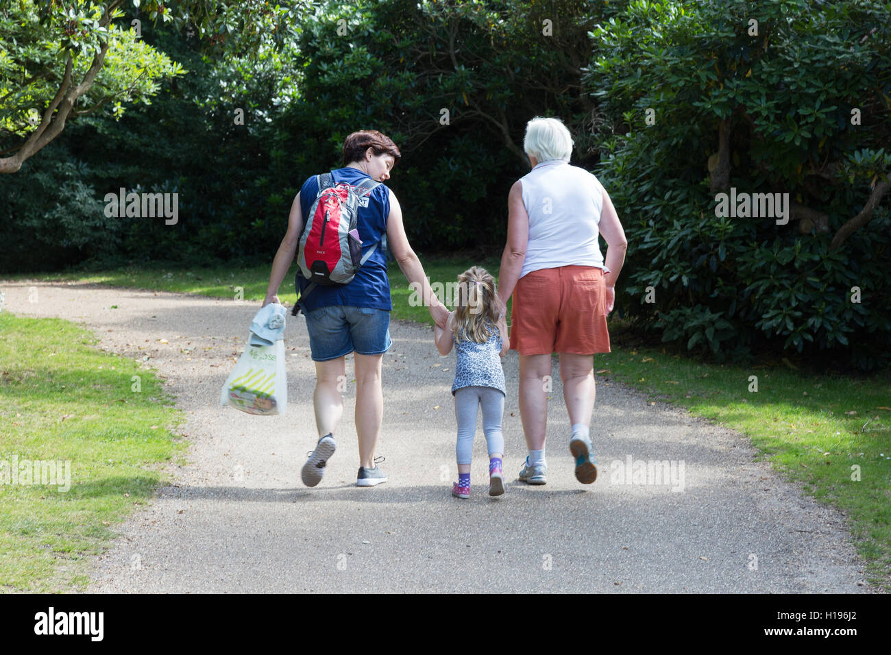Three generations of women; child, mother and grandmother walking in a park, seen from the back, UK - Stock Image