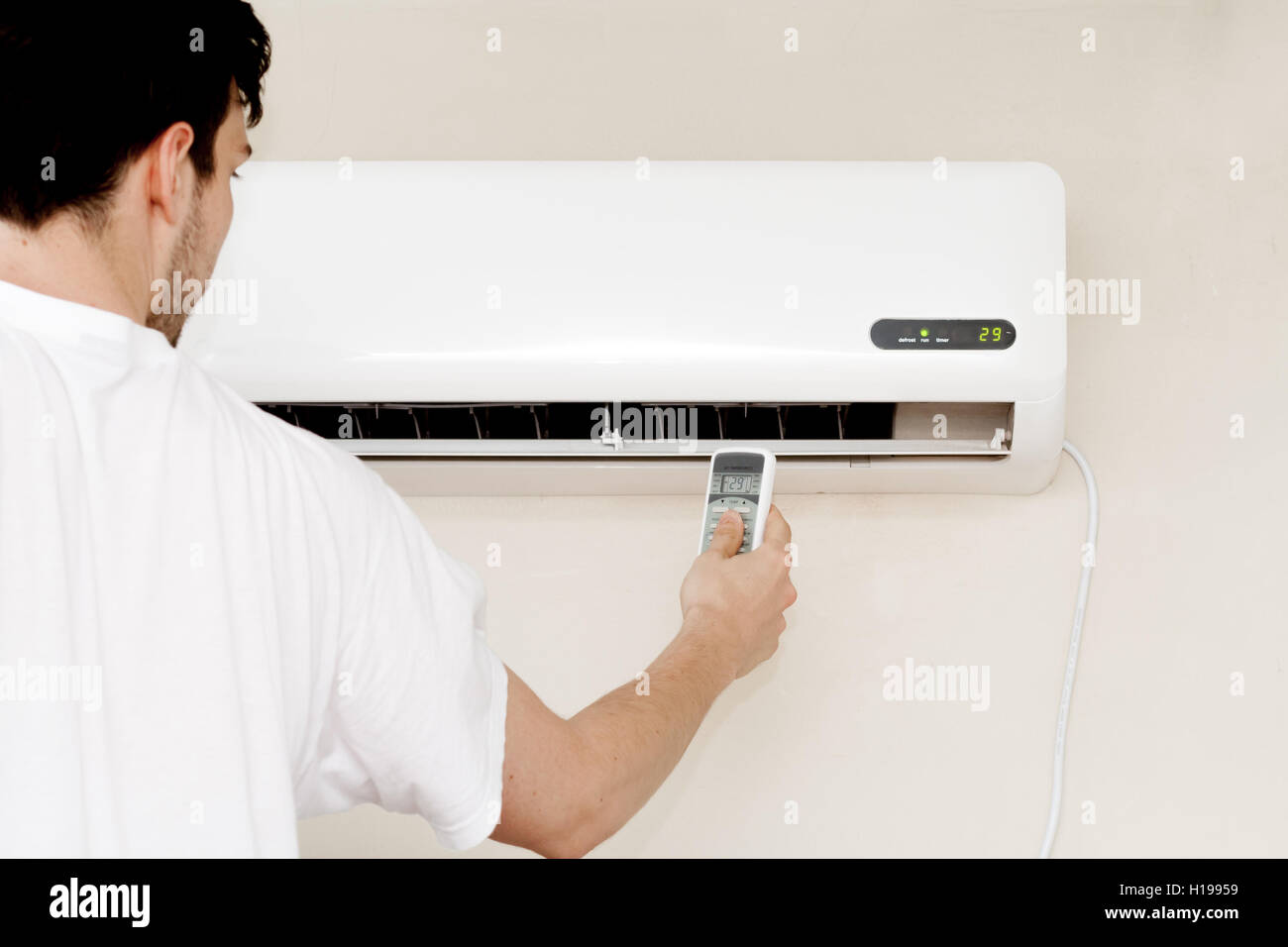 One man using remote air Conditioner indoors unit Stock Photo