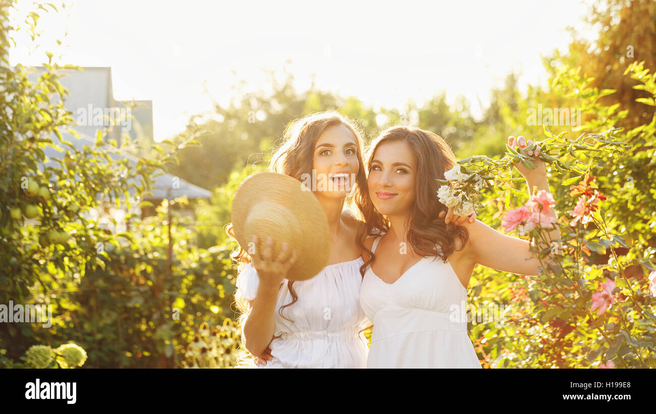 Two sisters. Girls hugging in the garden. Family time. Human relationships. Setting sun. - Stock Image