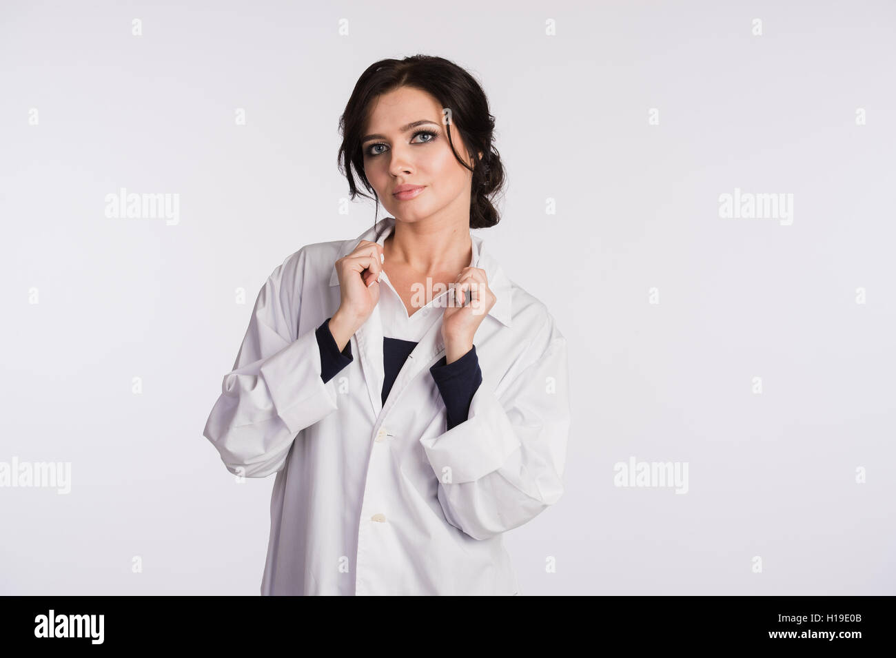 Woman doctor holding up her collar and standing against a white background - Stock Image
