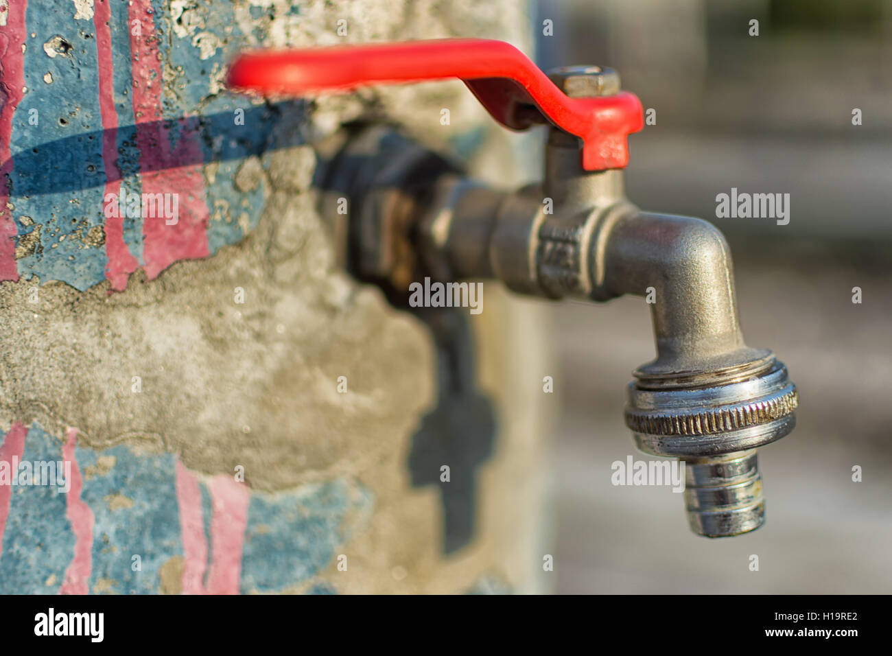 Faucet on Old Cracked Blue Painted Wall. Red Handle Water Tap Outdoor Background. Save Water Concept. - Stock Image