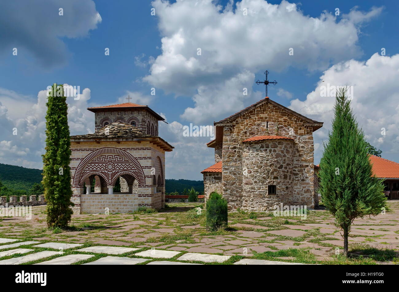 View of inner  yard with old medieval church, alcove and  bell tower  in restored Montenegrin or Giginski monastery Stock Photo