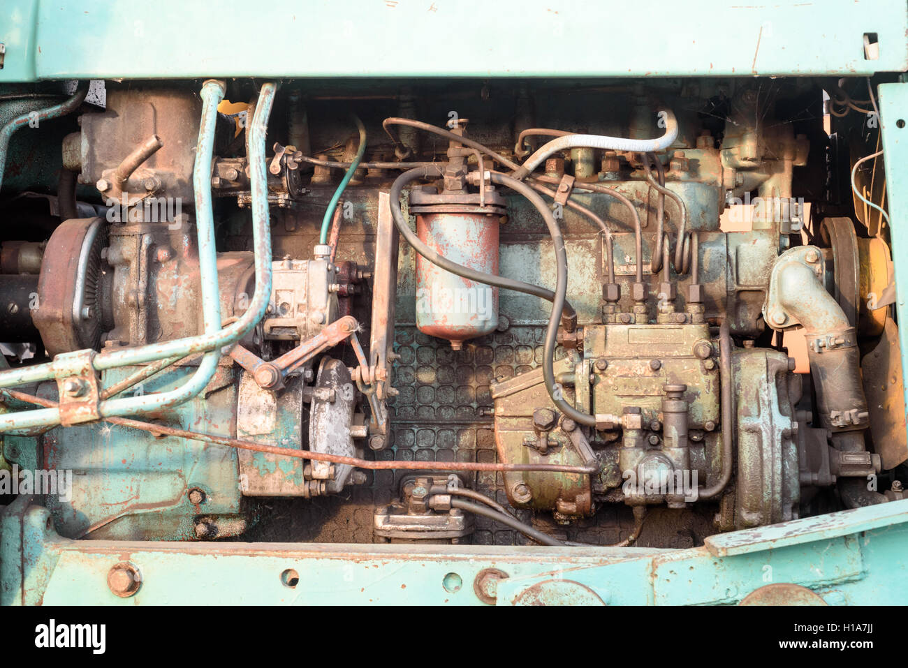 Old worn engine block of a large industrial machine in color showing the machines parts and fittings. - Stock Image