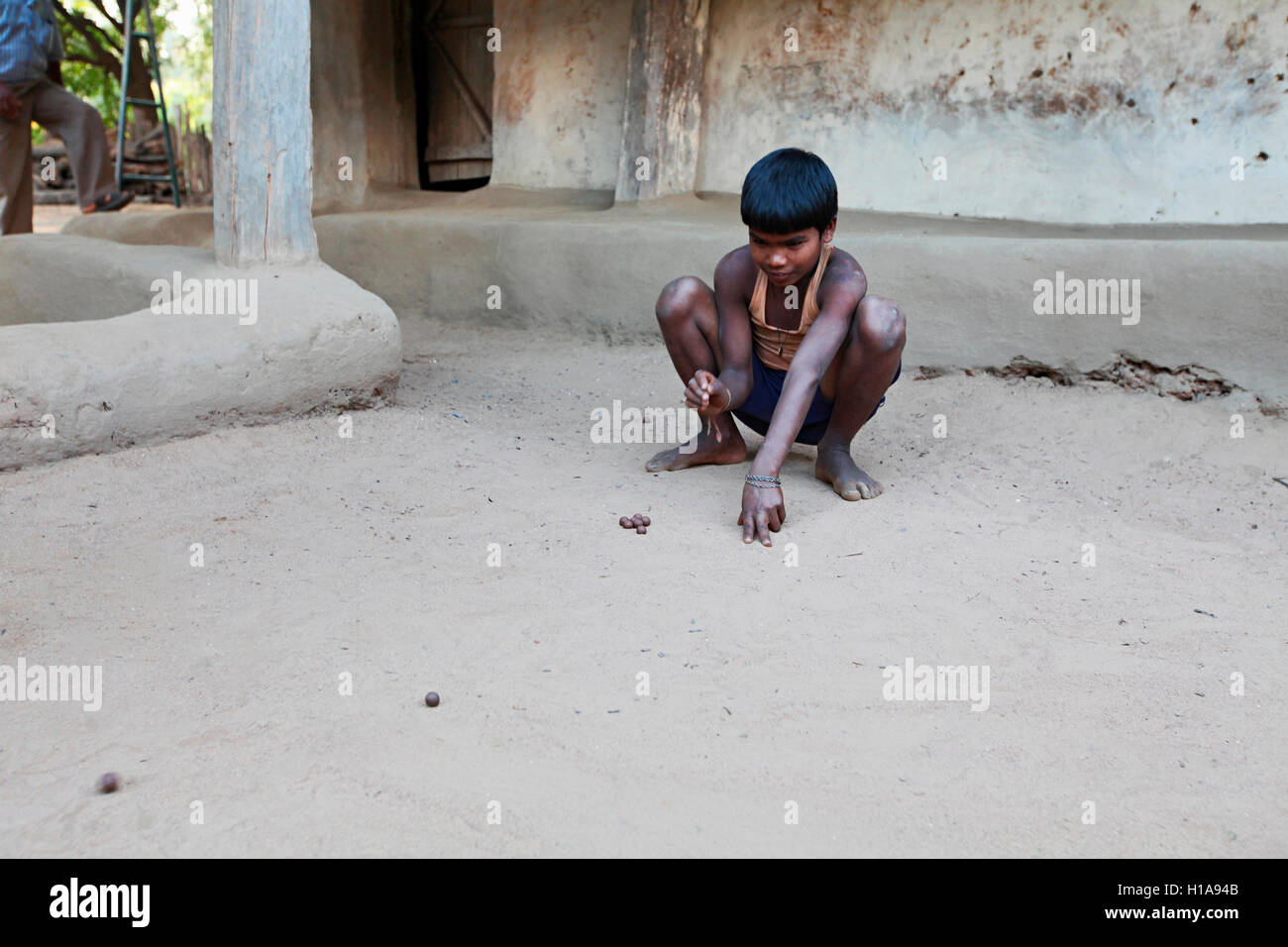 A child playing game of marbles, Erdku Village, Chattisgarh, India - Stock Image