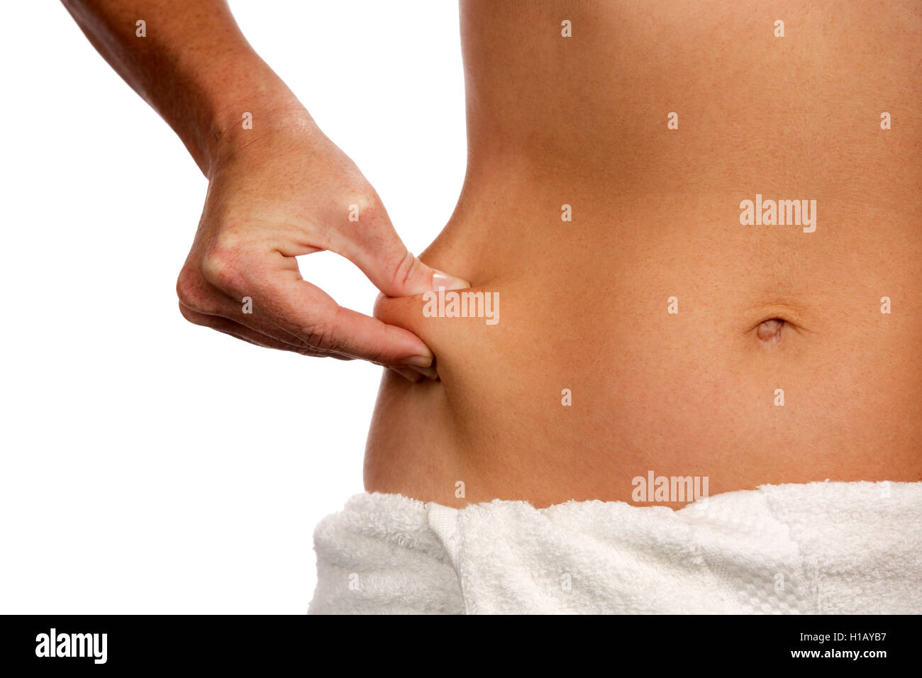 Thin woman pinches some excess flesh of her stomach at her waistline as a dieting and health concept. - Stock Image