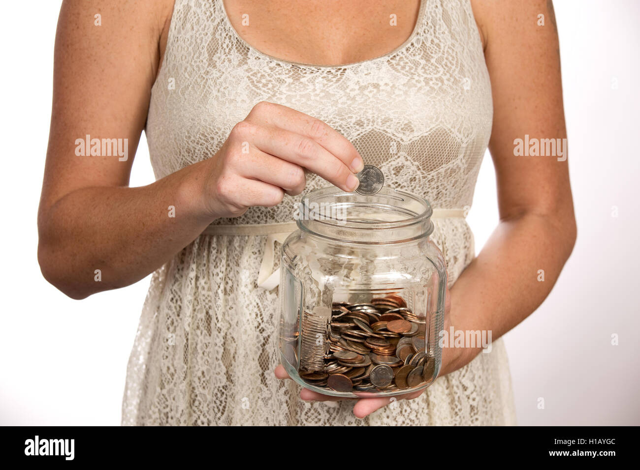Woman puts a quarter in a clear glass savings jar for use as a financial and banking concept. - Stock Image