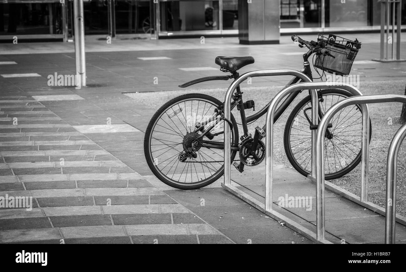 a black-and-white photo of a lonely bicycle parked in a desolate street - Stock Image