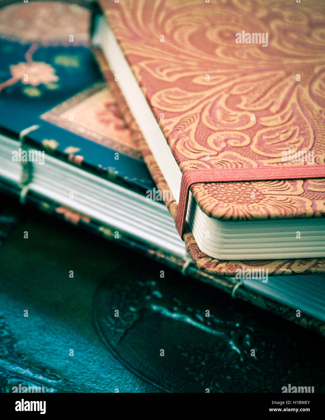 a pile of various beautiful journals and diaries - Stock Image