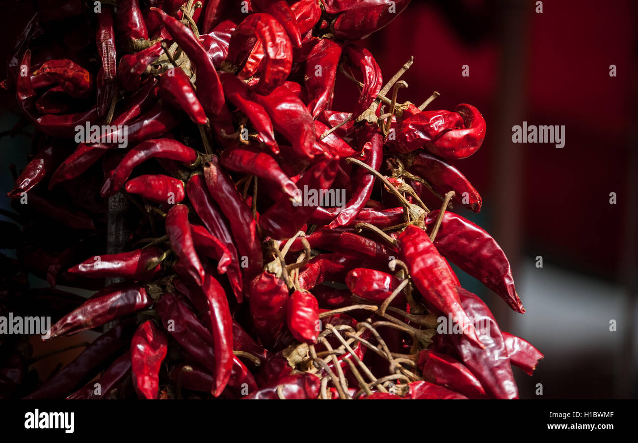 close-up photo of a bunch of red chili peppers in a market - Stock Image