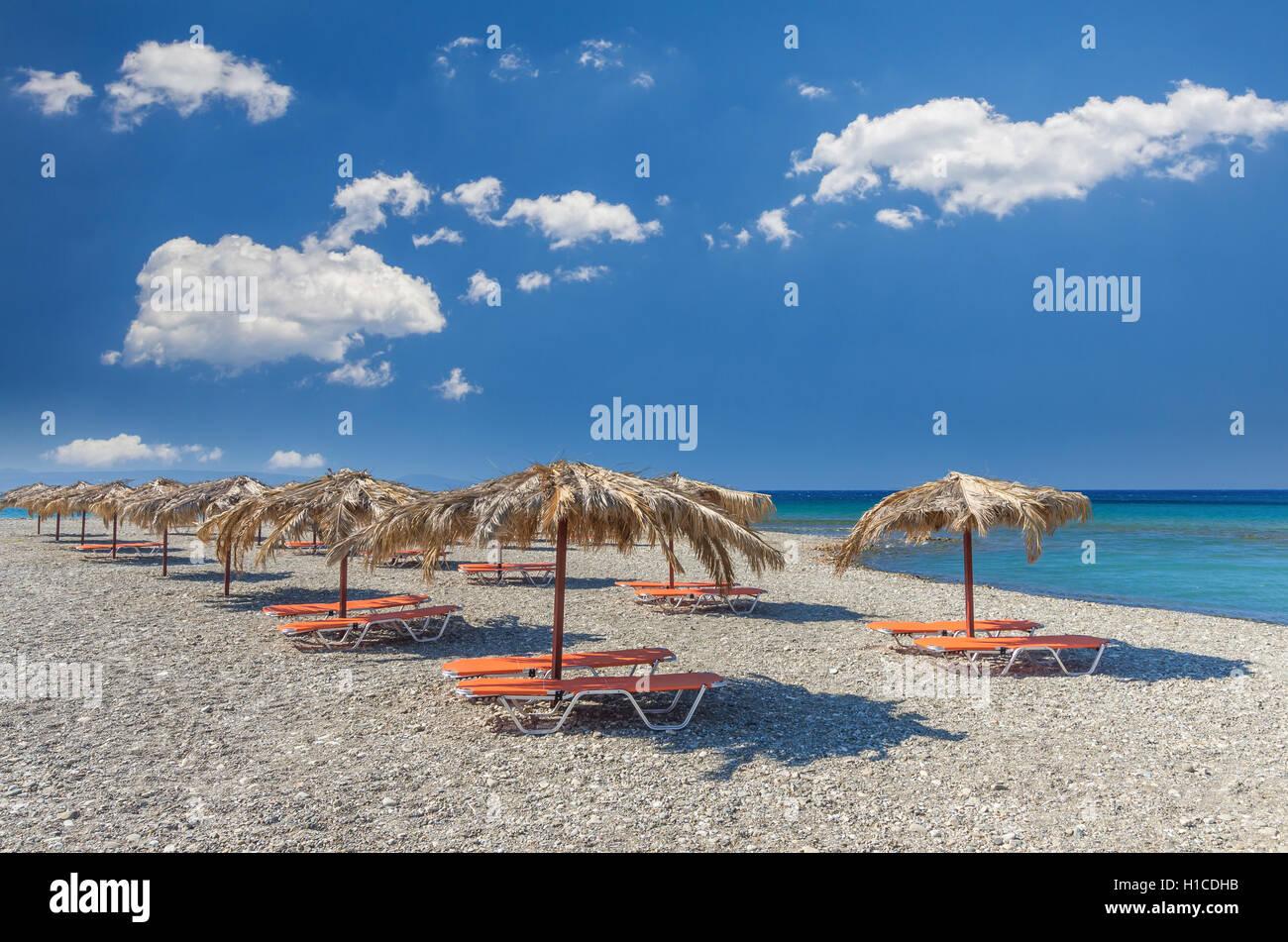 Straw umbrella on a sandy beach in Greece. Beach chairs with umbrellas on a beautiful beach in Crete island. Stock Photo