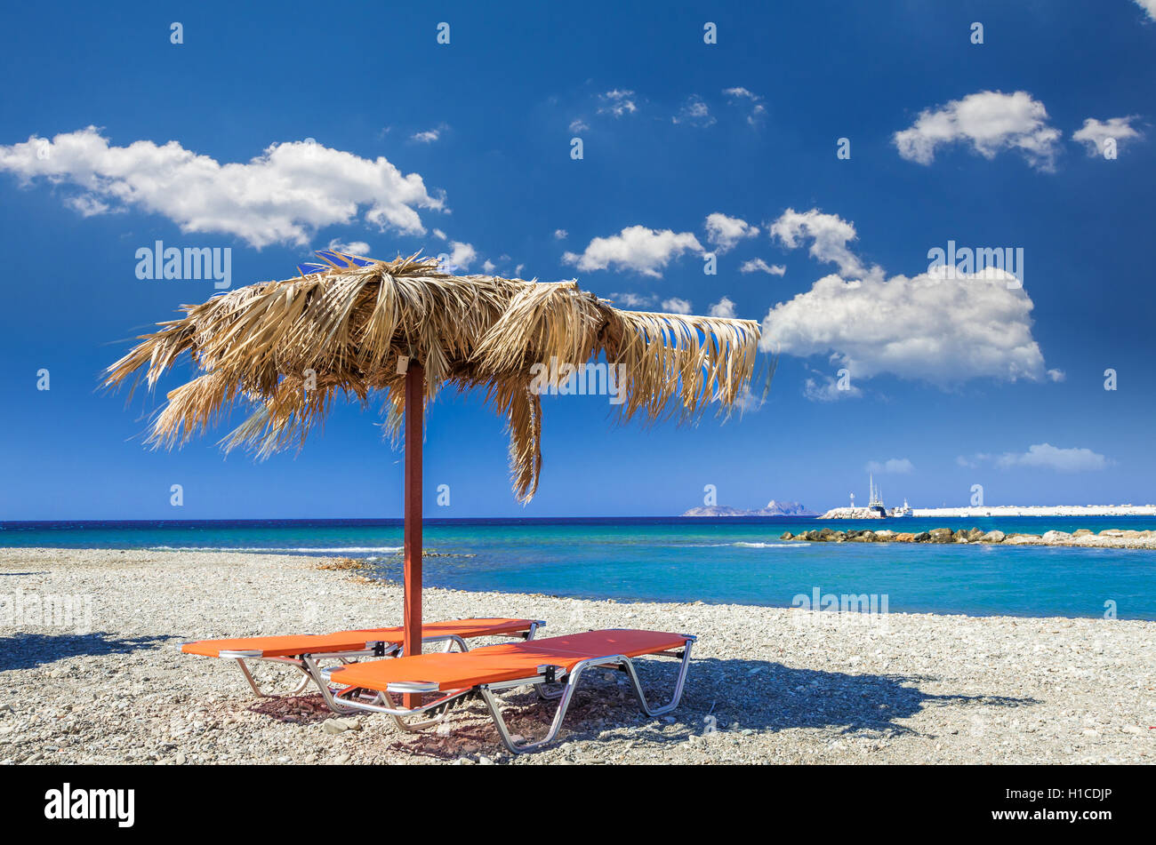 Straw umbrella on a sandy beach in Greece. Beach chairs with umbrellas on a beautiful beach in Crete island. - Stock Image