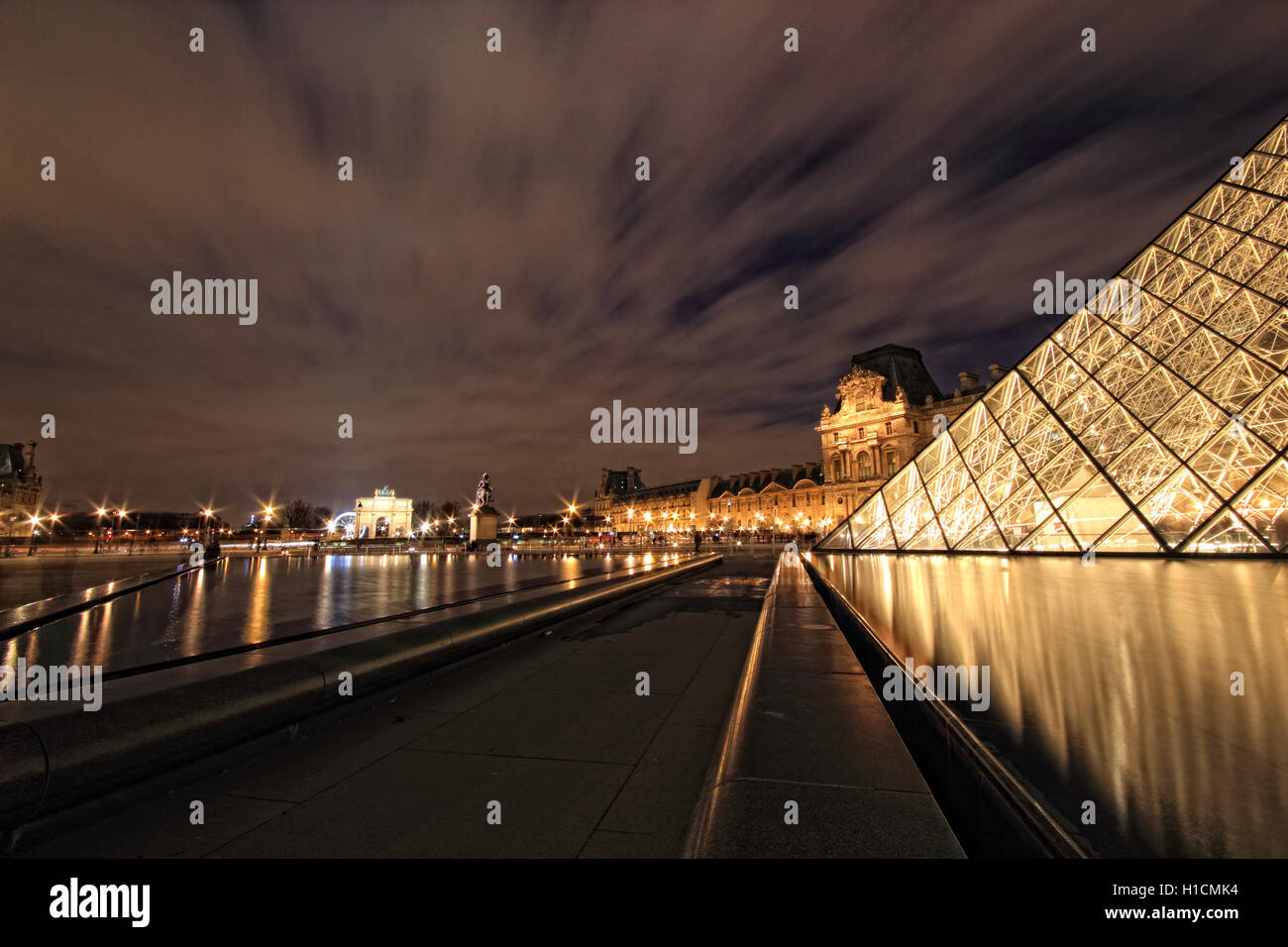 PARIS - January 8th 2012 : Closeup of Louvre Pyramid shined at dusk in Paris, France. Louvre is the biggest Museum Stock Photo