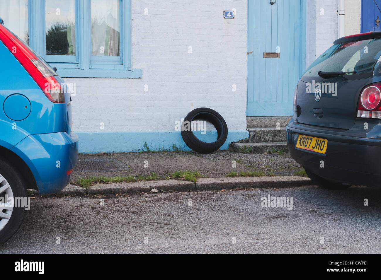 A car tyre dumped by the front of a residential house in Falmouth, Cornwall - Stock Image