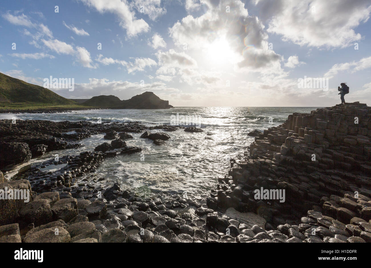 Tourist taking picture in Giant's Causeway at sunset, Bushmills, County Antrim, Northern Ireland, UK - Stock Image