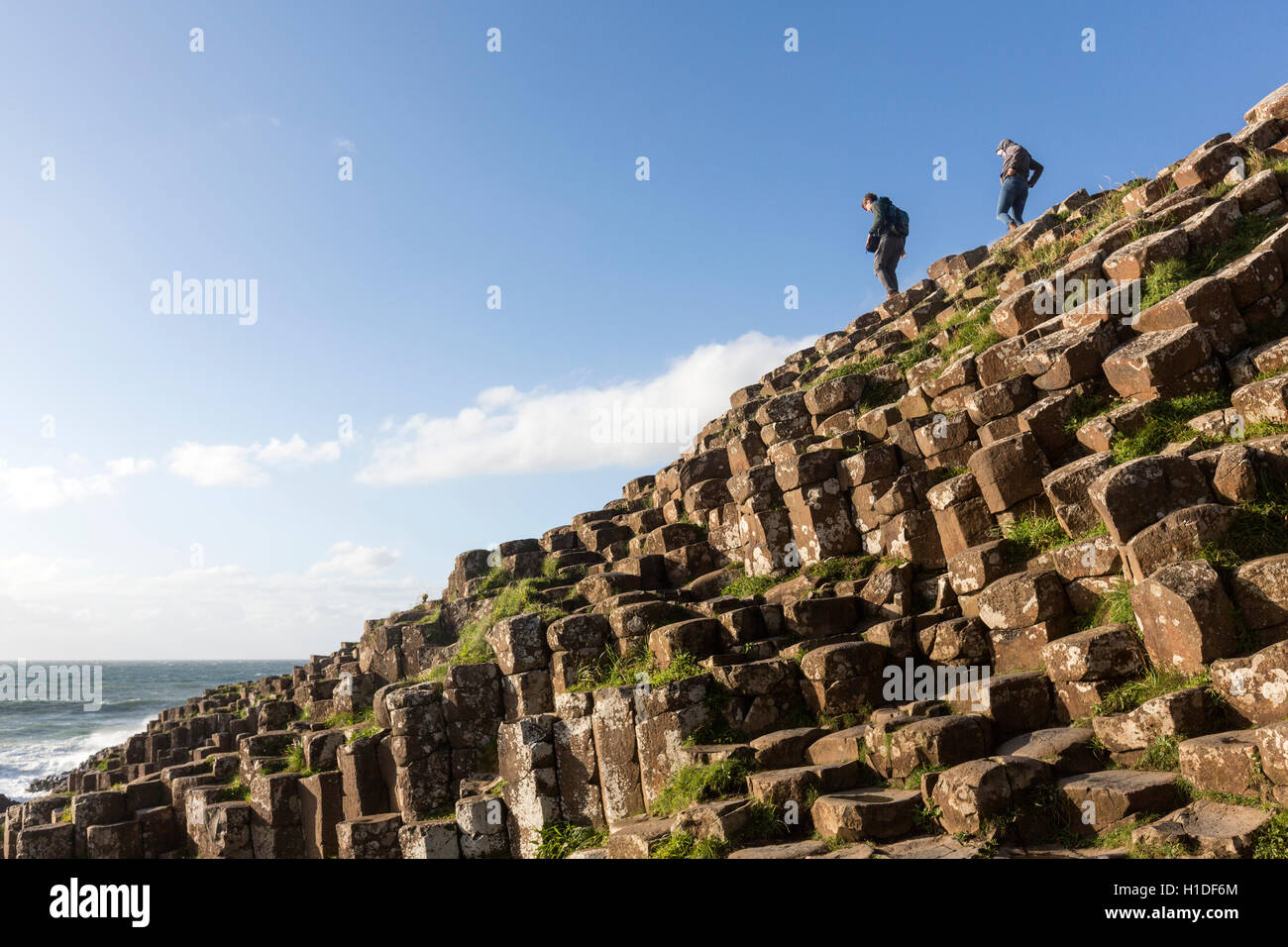 Tourist standing on basalt columns in Giant's Causeway, Bushmills, County Antrim, Northern Ireland, UK - Stock Image