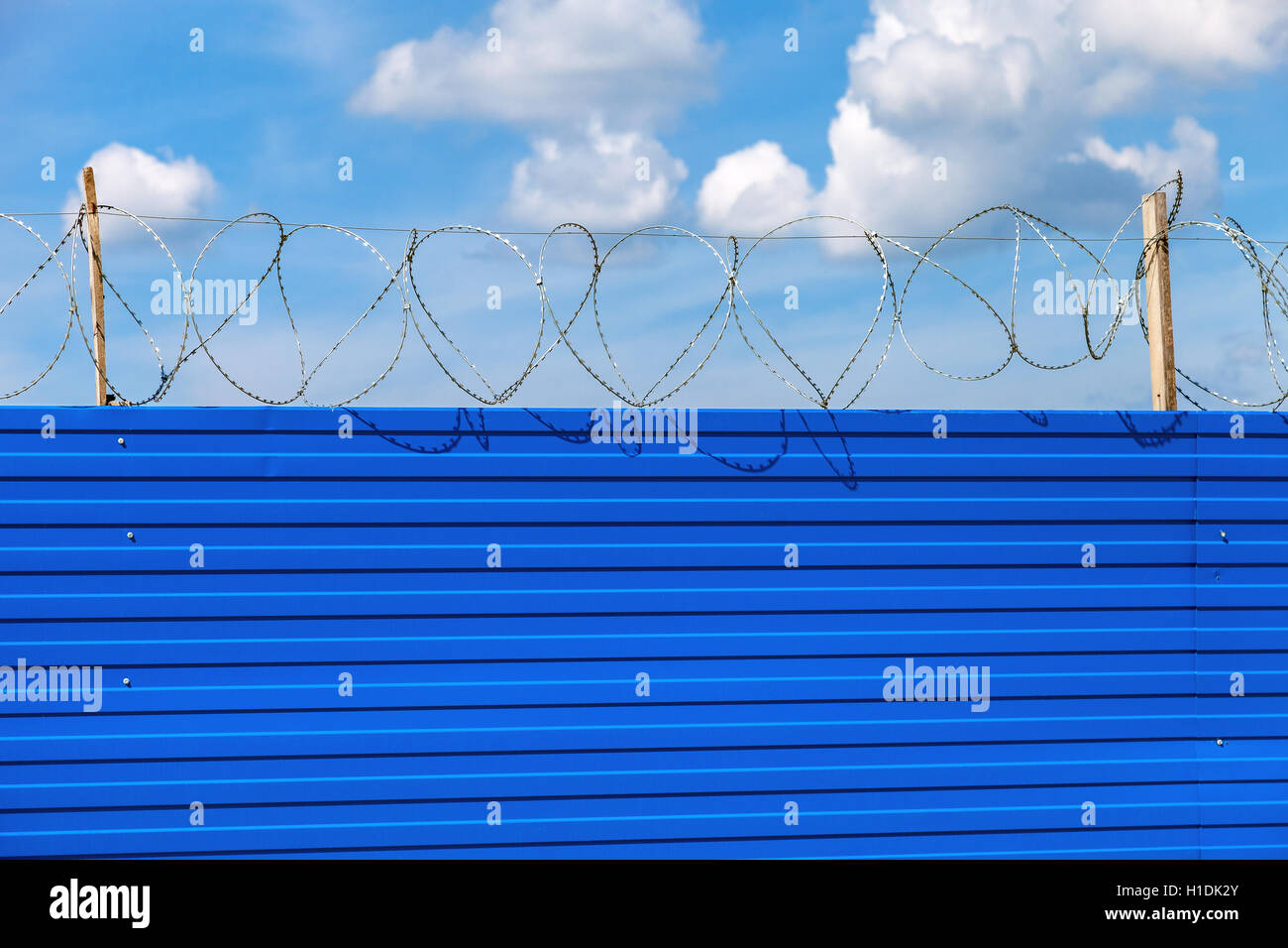 Barbed wire on the fence against a blue sky background. Restricted area - Stock Image