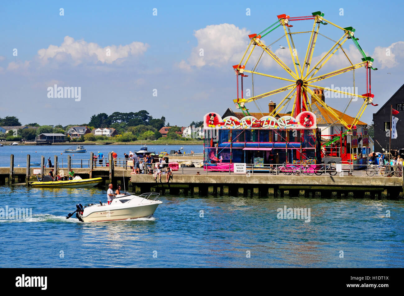 motor boat cruising past  mudeford quay in front of ferris wheel and kiddies play area. - Stock Image