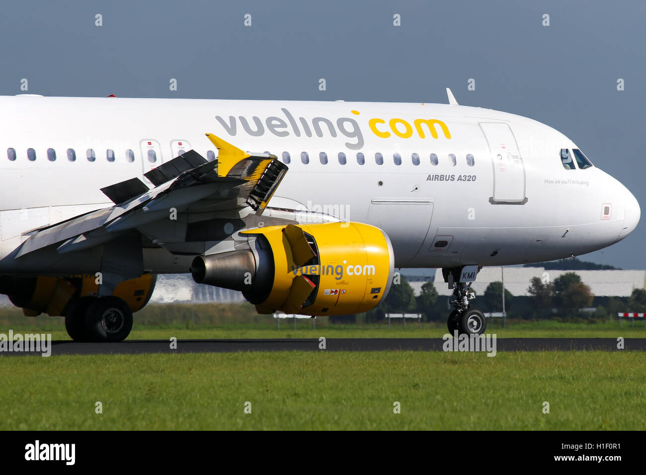 Vueling Airbus A320 touches down on runway 18R at Amsterdam Schipol airport. - Stock Image