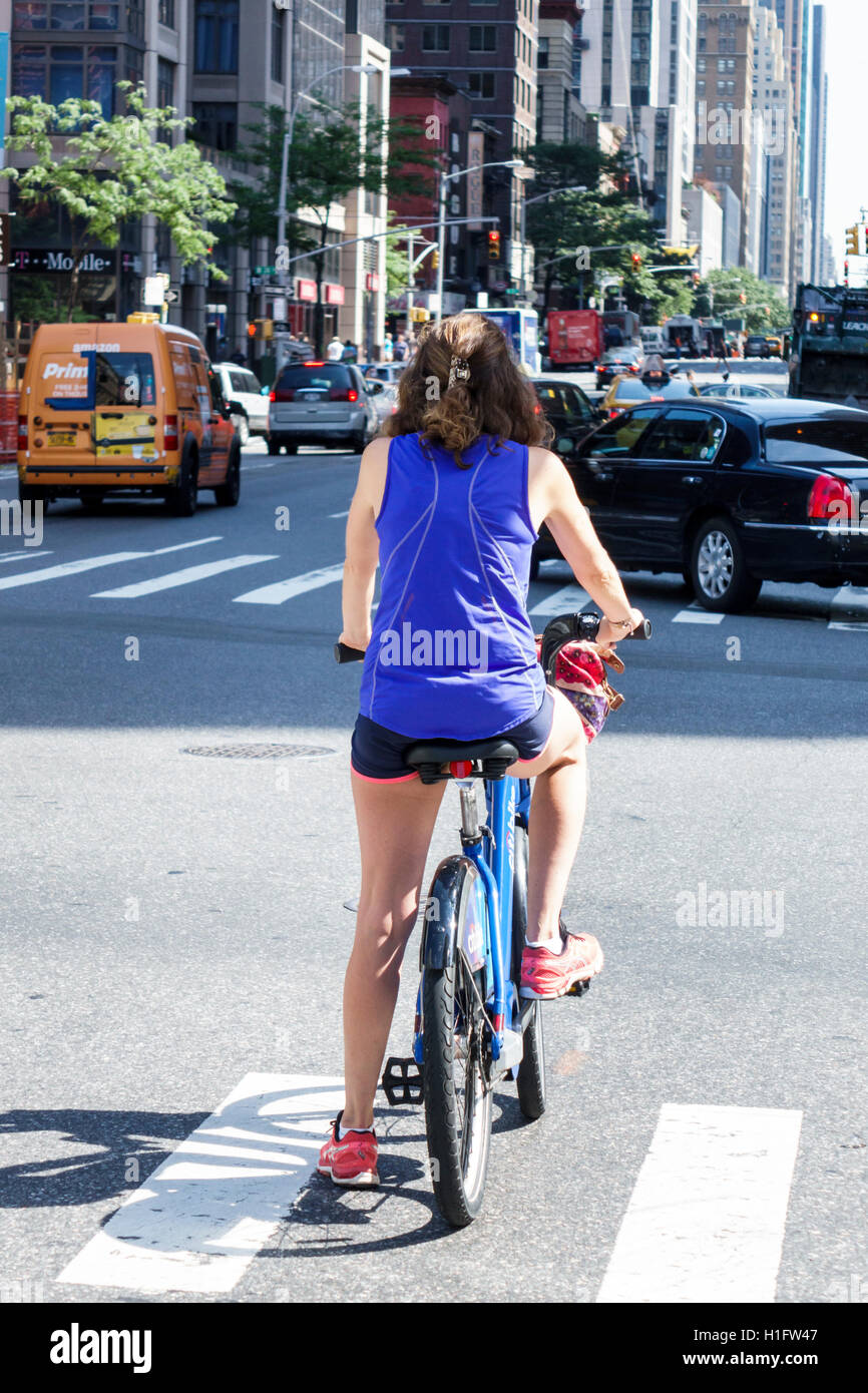 Manhattan New York City NYC NY Chelsea 6th Sixth Avenue street traffic woman bicycle cycle stopped intersection Stock Photo