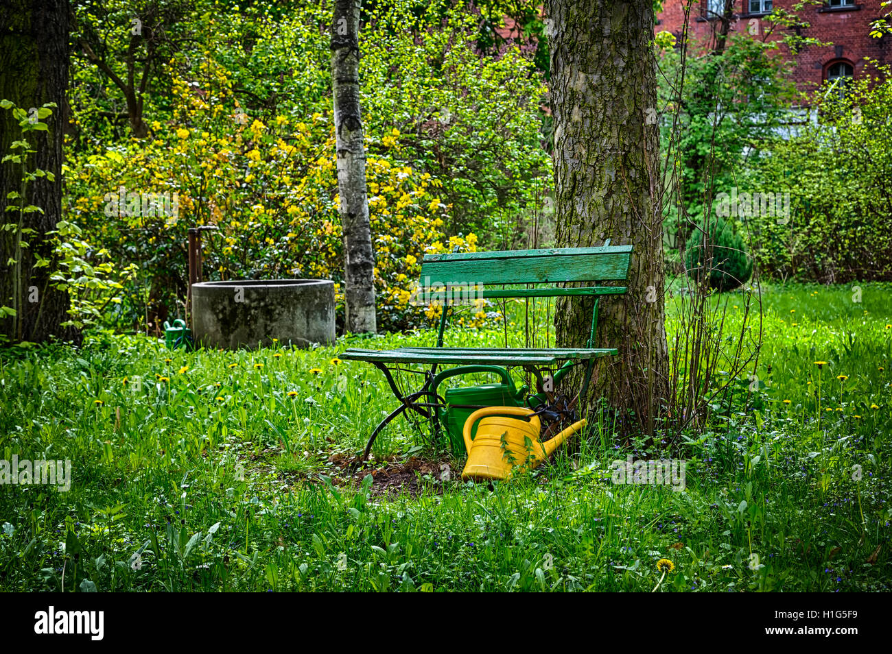 garden bench with yellow ewer - Stock Photo