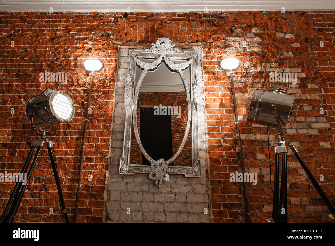 Old ornate frames on mirror glas hanging on a brick wall. - Stock Image