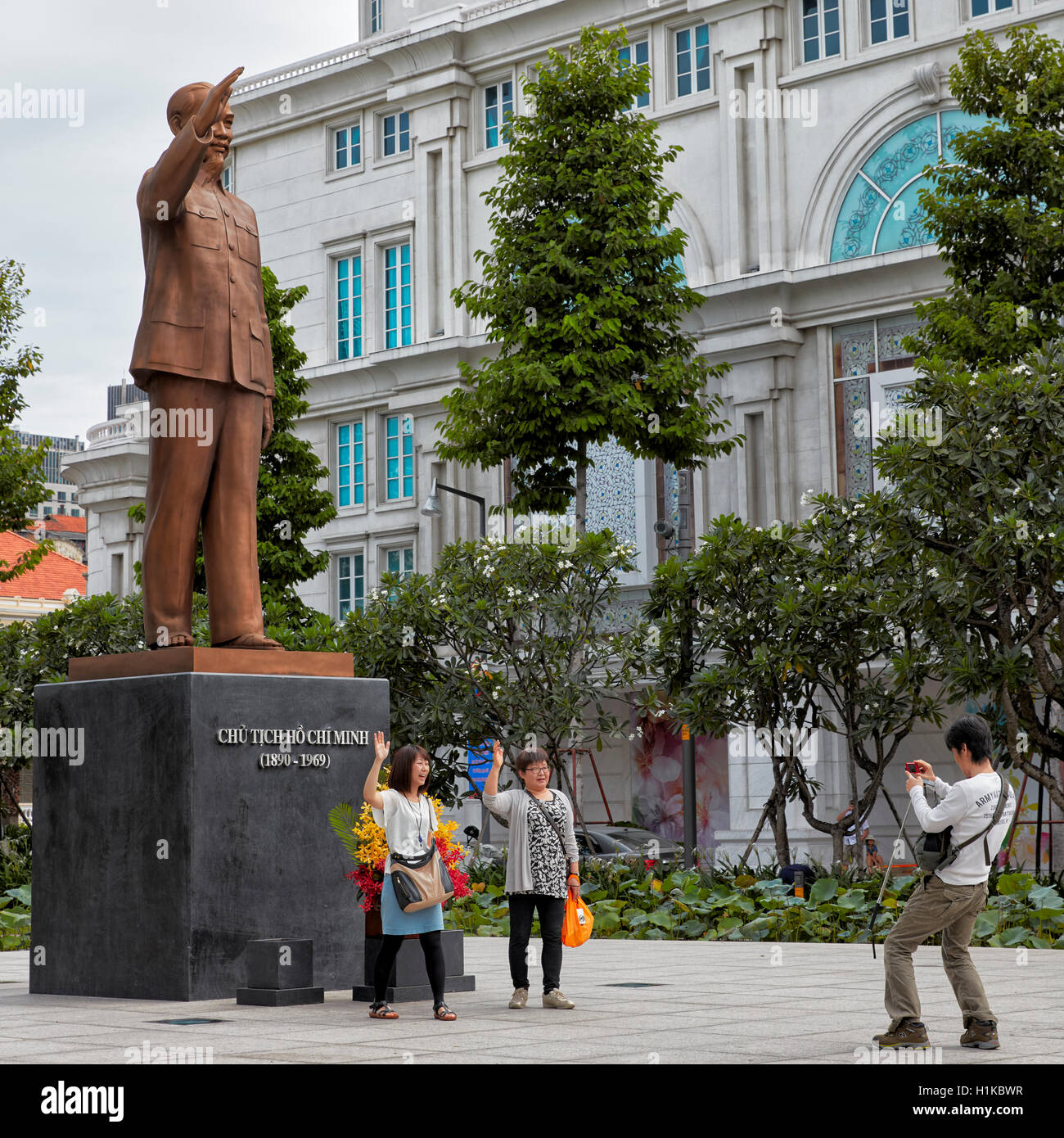 Tourists take photo in front of Ho Chi Minh Statue. Ho Chi Minh City, Vietnam. - Stock Image