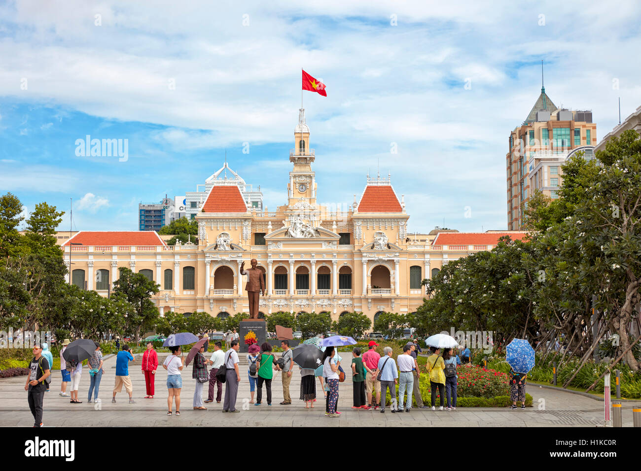Tourists at Ho Chi Minh Statue in front of People's Committee Building. Ho Chi Minh City, Vietnam. - Stock Image