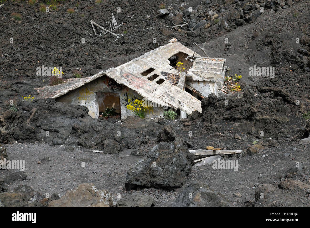 House covered with lava on the slopes of Mount Etna, Sicily, Italy - Stock Image