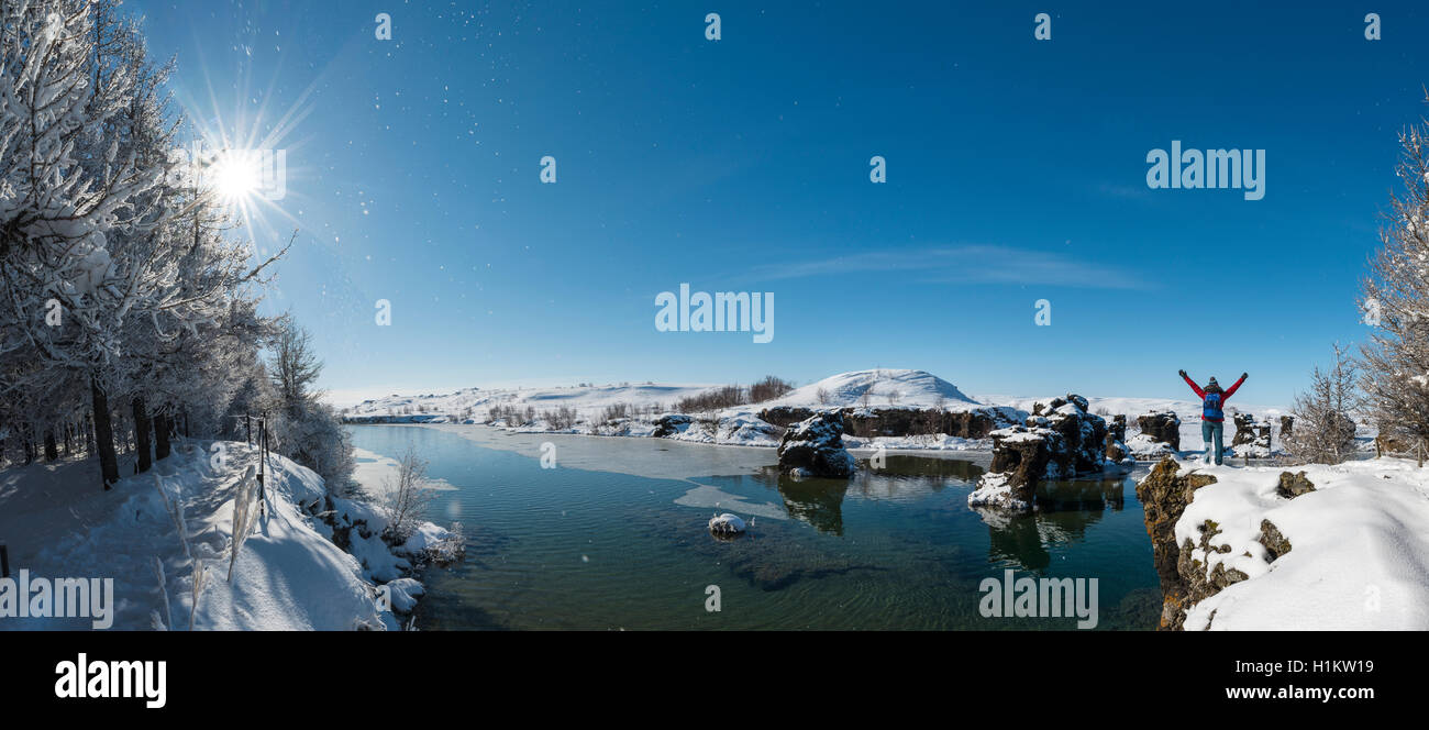 Hiker with arms in the air, overlooking Lake Mývatn in winter, Iceland - Stock Image