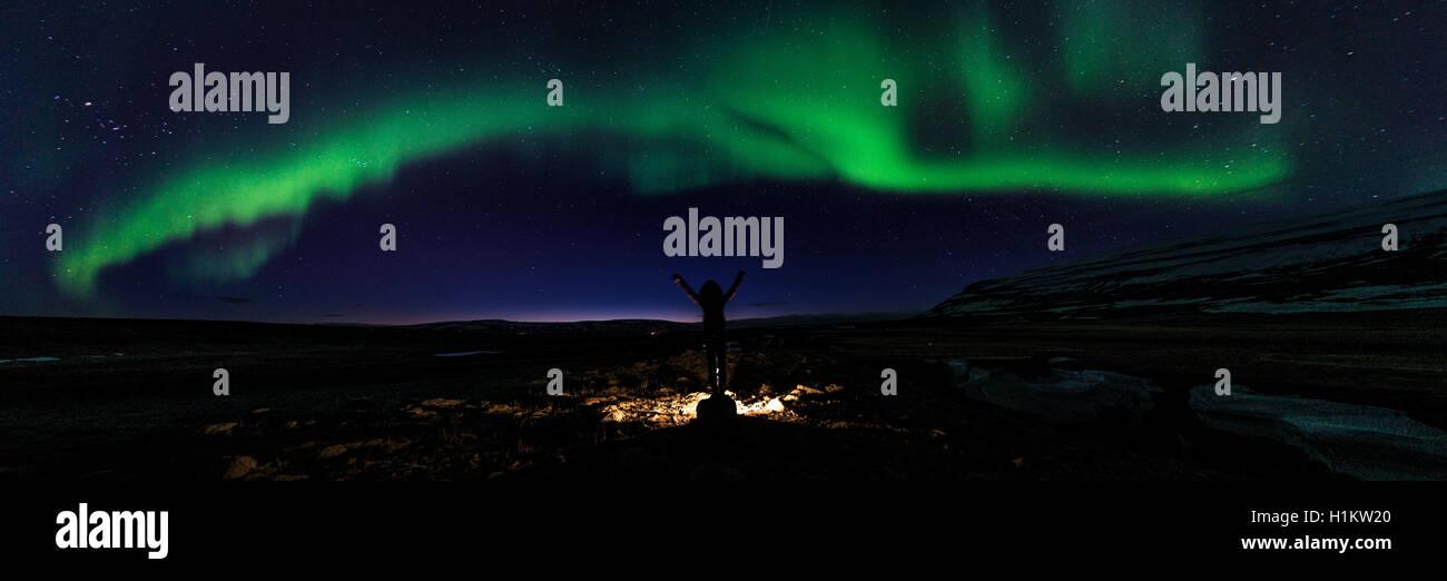 Young woman stretching arms upwards, starry sky, northern lights, aurora borealis, near Kolugljúfur, Northwestern - Stock Image
