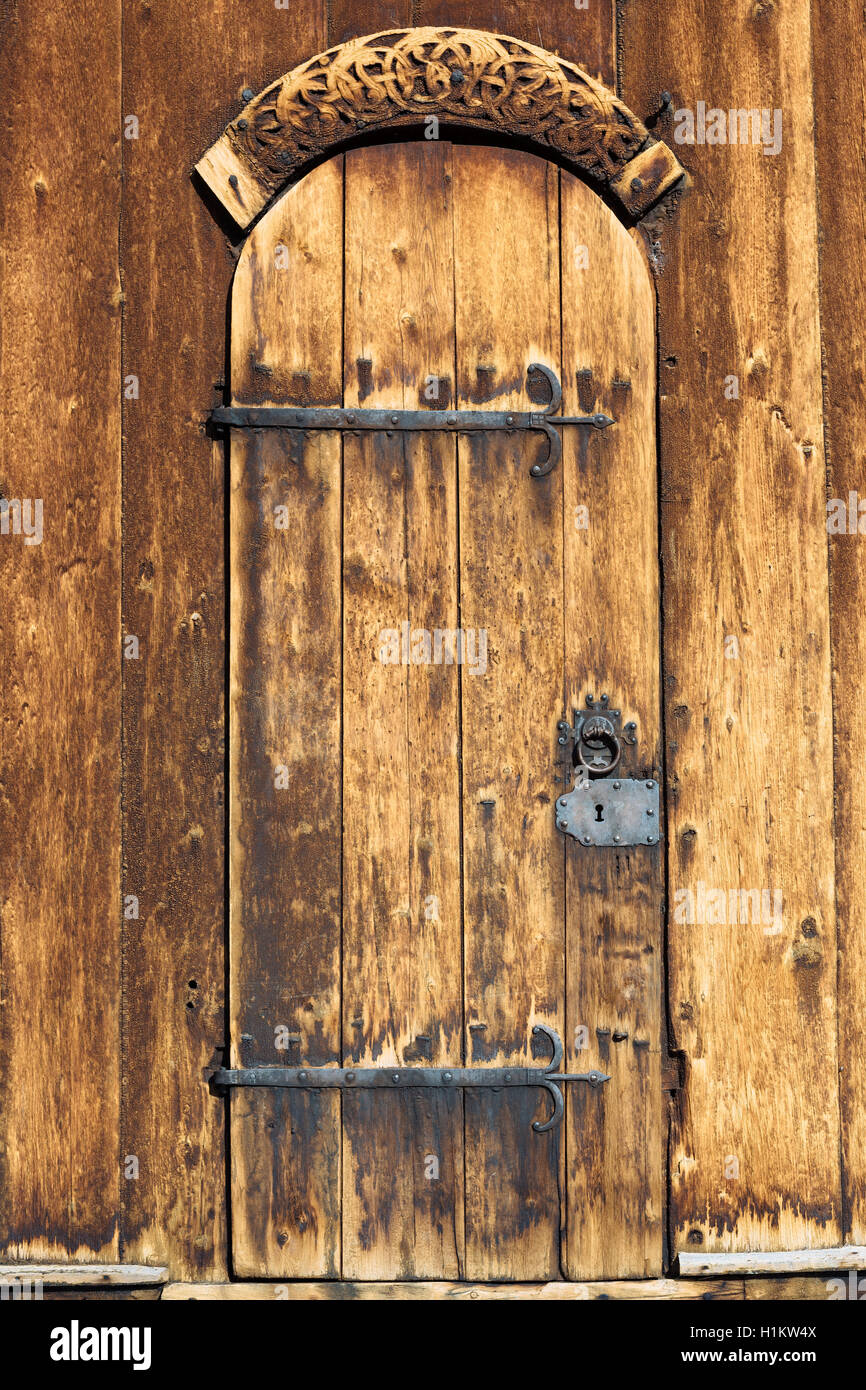 Door with iron fittings and wooden relief, Stave Church Lom, Lom, Oppland, Norway - Stock Image