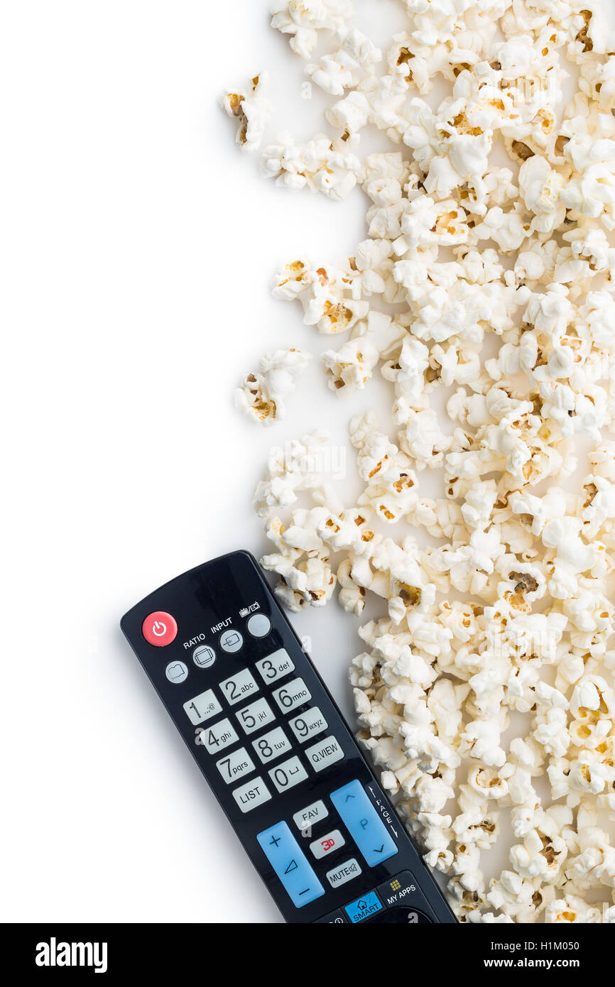 Tasty popcorn and tv remote control. Top view. - Stock Image