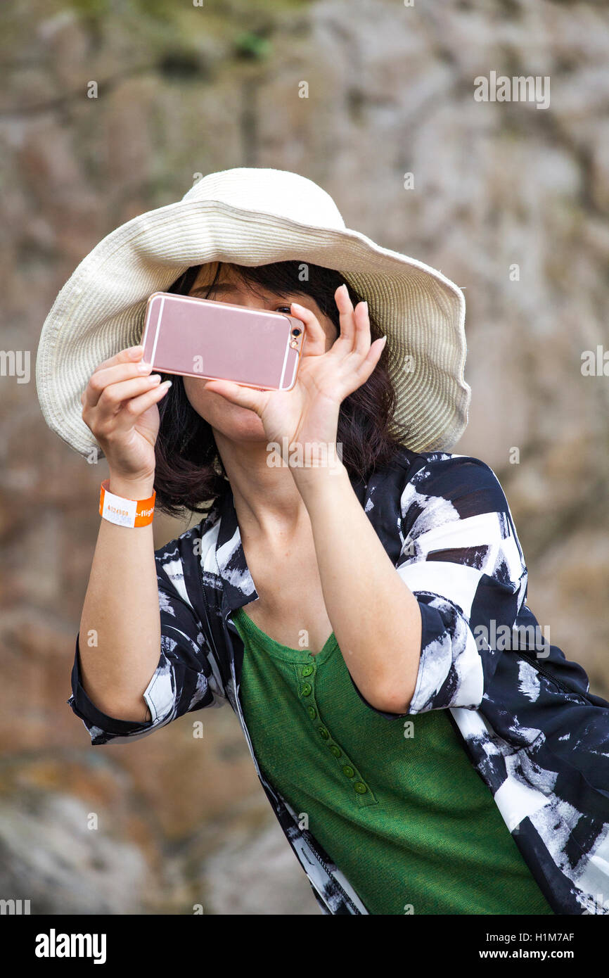 Japanese woman tourist photographing a bird at the KL Bird Park in Kuala Lumpur, Malaysia using her smartphone. - Stock Image