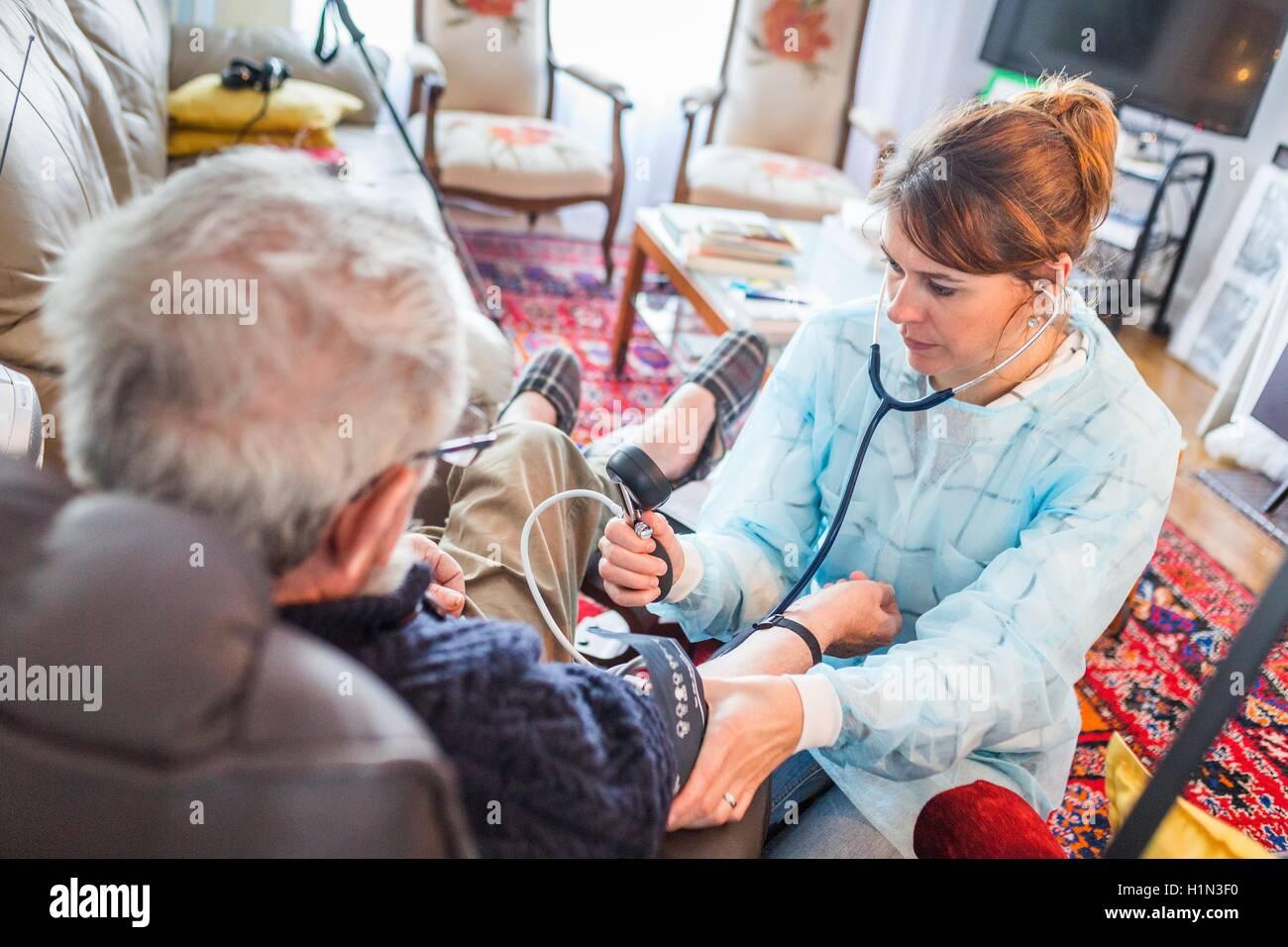 Nurse home visit, blood pressure taking of a patient, Home medical care department of Limoges hospital, France. - Stock Image