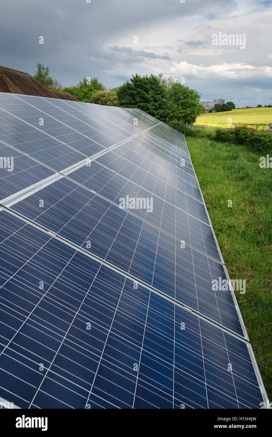 Kent, UK. An array of solar panels (PV or photo-voltaic) installed on a farm - Stock Image