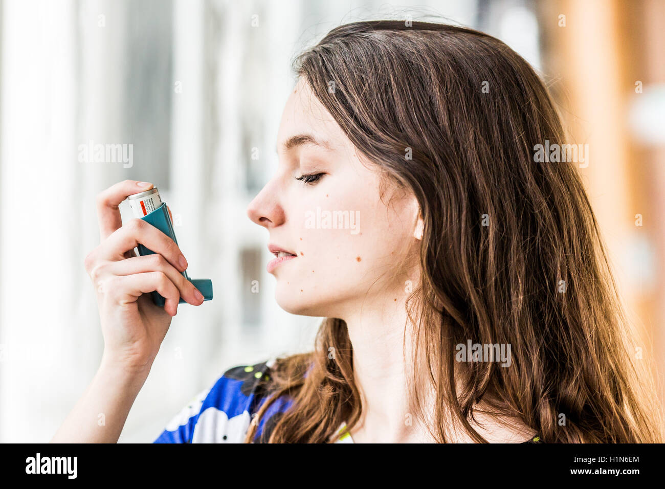 Tennage girl using an aerosol inhaler that contains bronchodilator for the treatment of asthma. - Stock Image