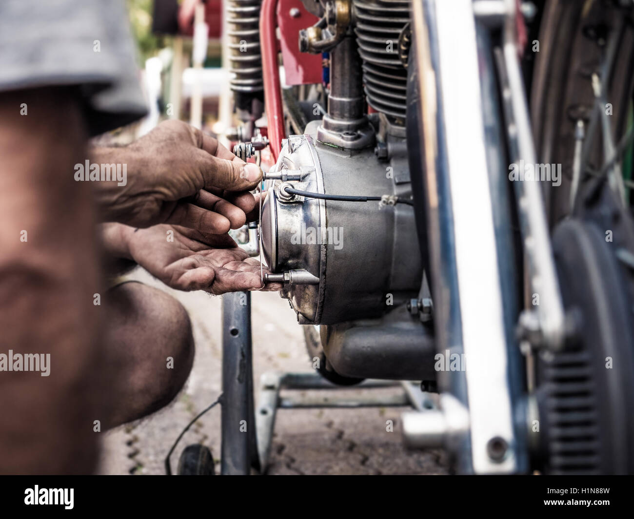 Mechanic with dirty hands fixing a screw on a old bike engine, intentional blur and vivid colors. - Stock Image
