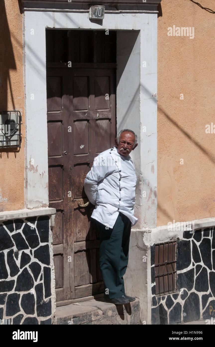 Bolivian barber standing in his doorway, Potosi - Stock Image