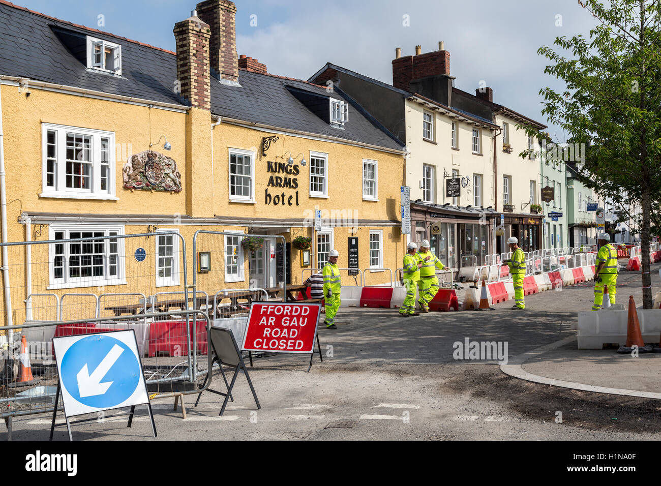 Workmen standing outside Kings Arms Hotel with road closed sign, Abergavenny, Wales, UK - Stock Image