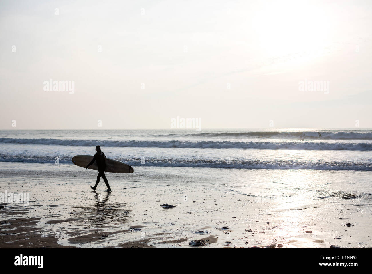 Surfer carrying a surfboard silhouetted against the sea ans sky walking on a UK beach - Stock Image