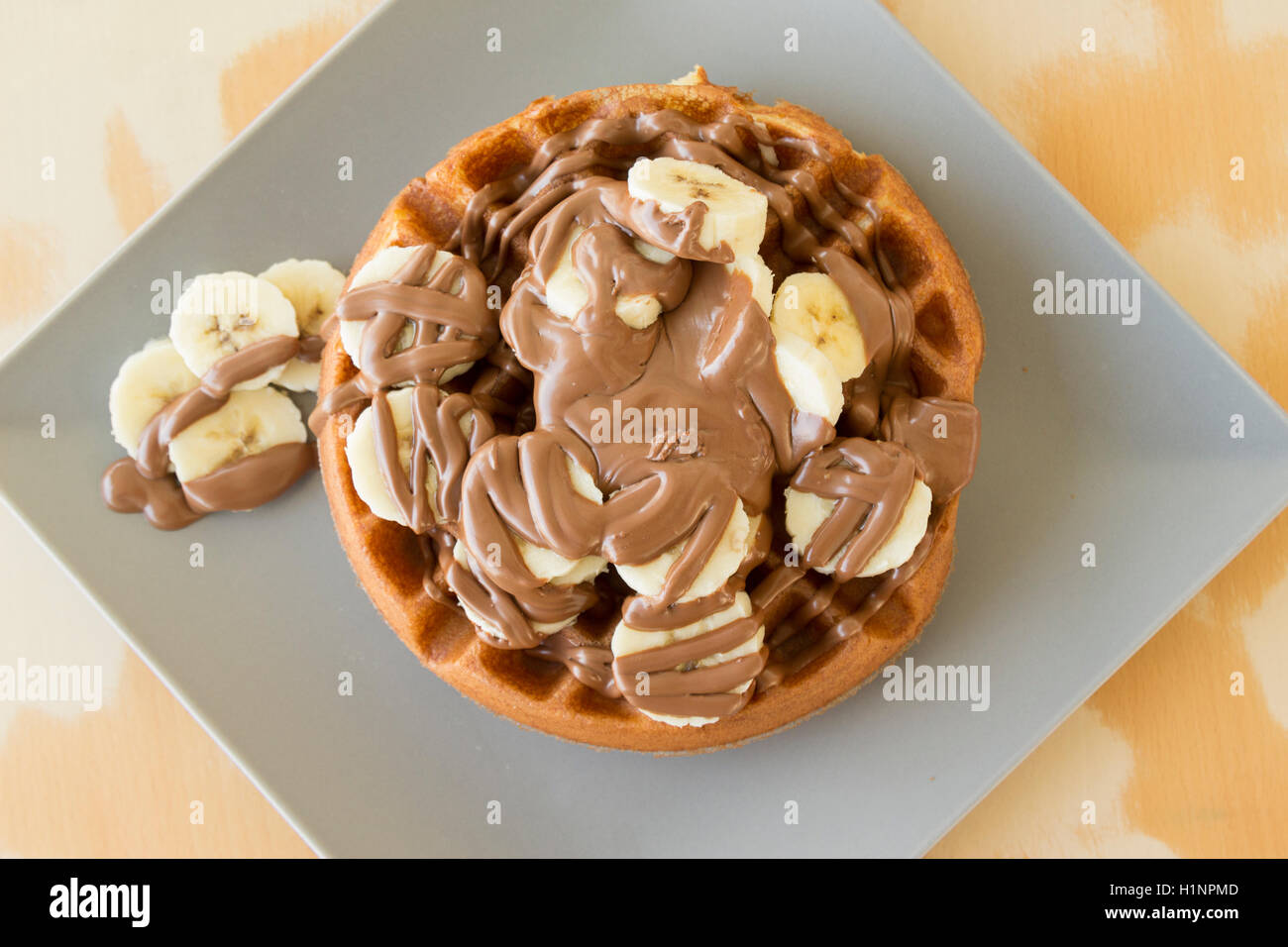 Tasty waffle with banana slices and chocolate cream on the top served in a plate - Stock Image