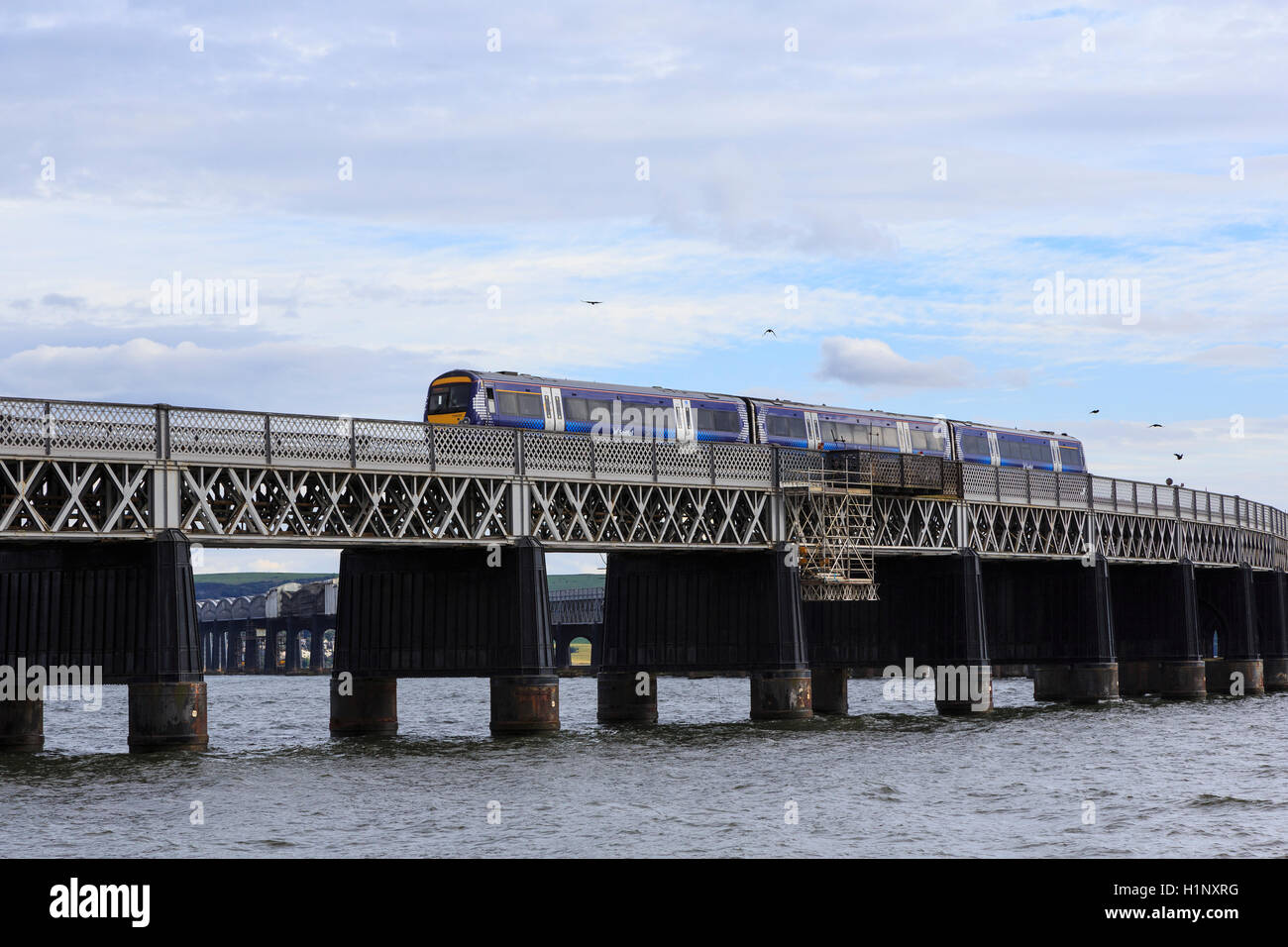 Tay Rail Bridge, north end, Dundee, Scotland, with a Scotrail diesel multiple unit  (DMU) crossing. - Stock Image