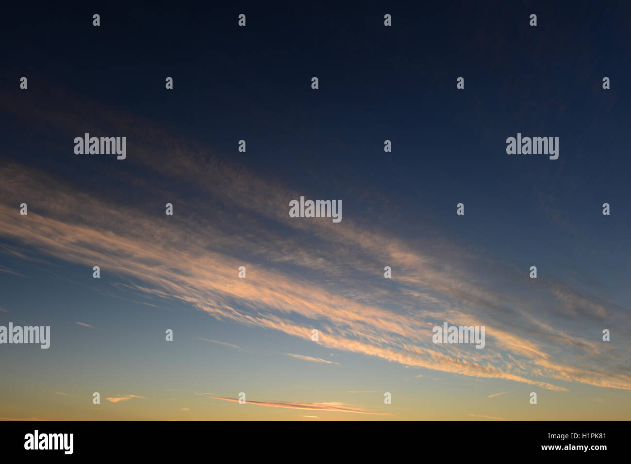 Bright blue sky at sunset autumn sun with white clouds - Stock Image