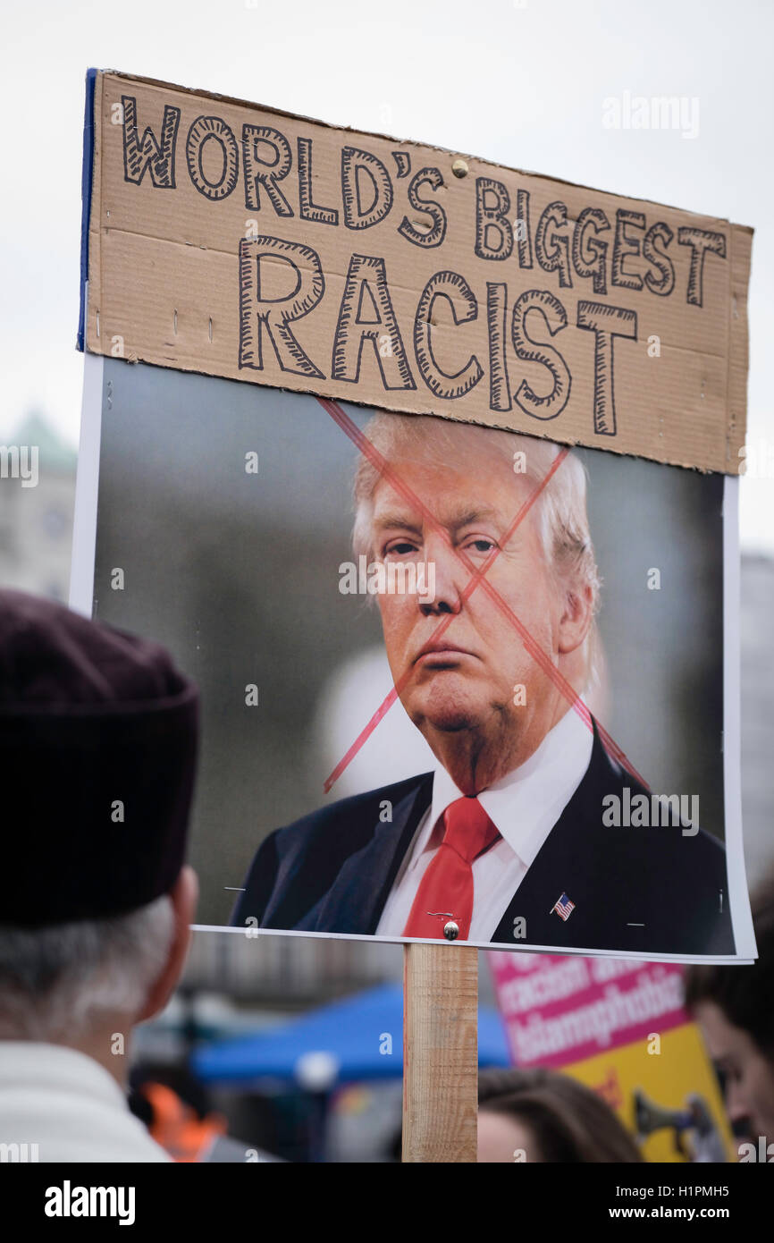 Man holding a placard declaring Trump as the worlds biggest racist in Trafalgar square at an anti-racism protest - Stock Image