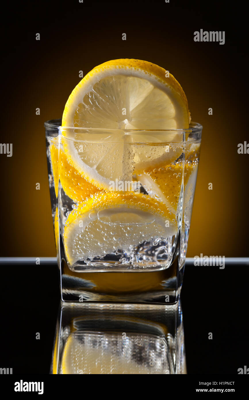 Glass of alcoholic drink with lemon on a reflective background - Stock Image