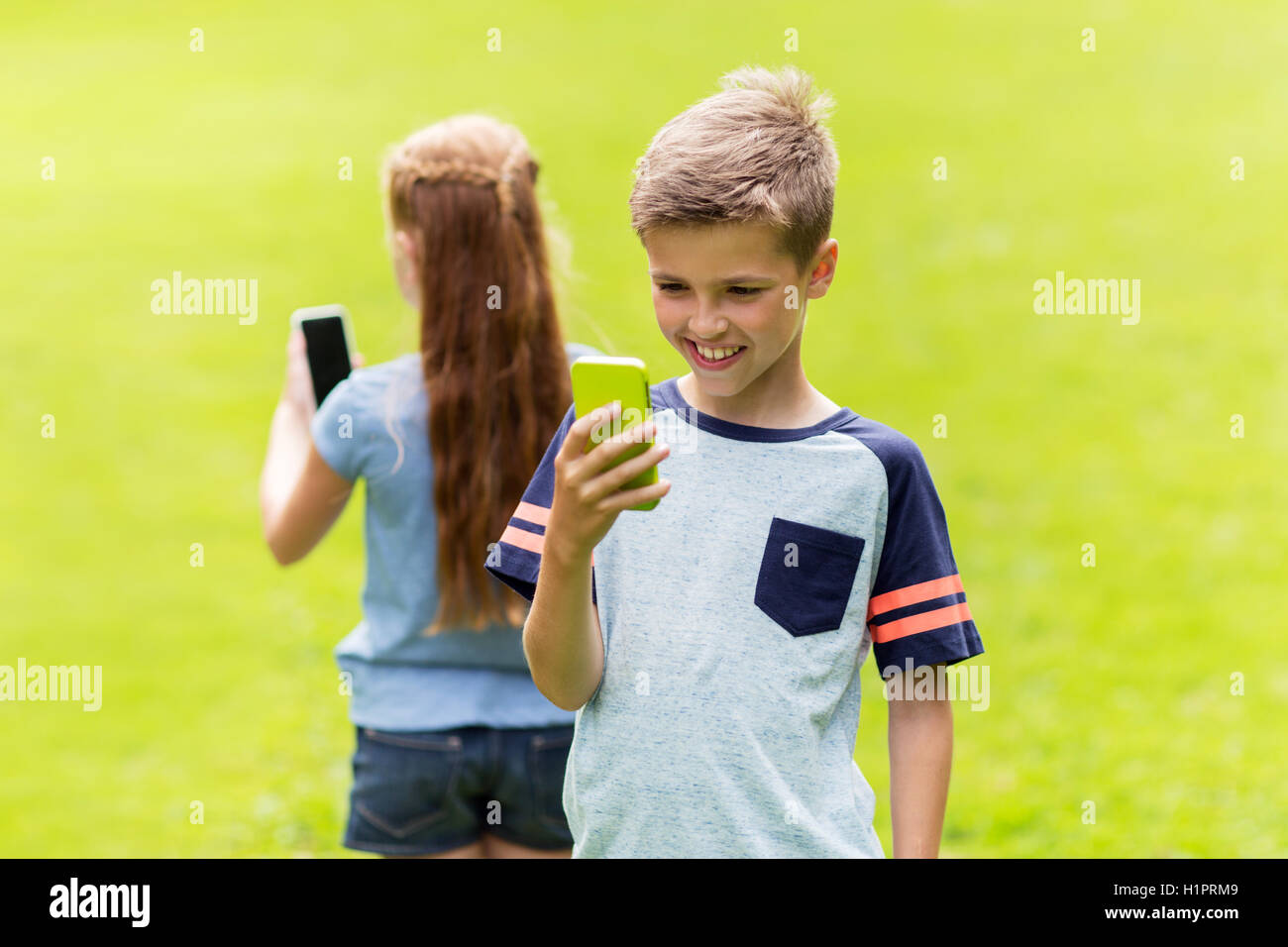 kids with smartphones playing game in summer park - Stock Image