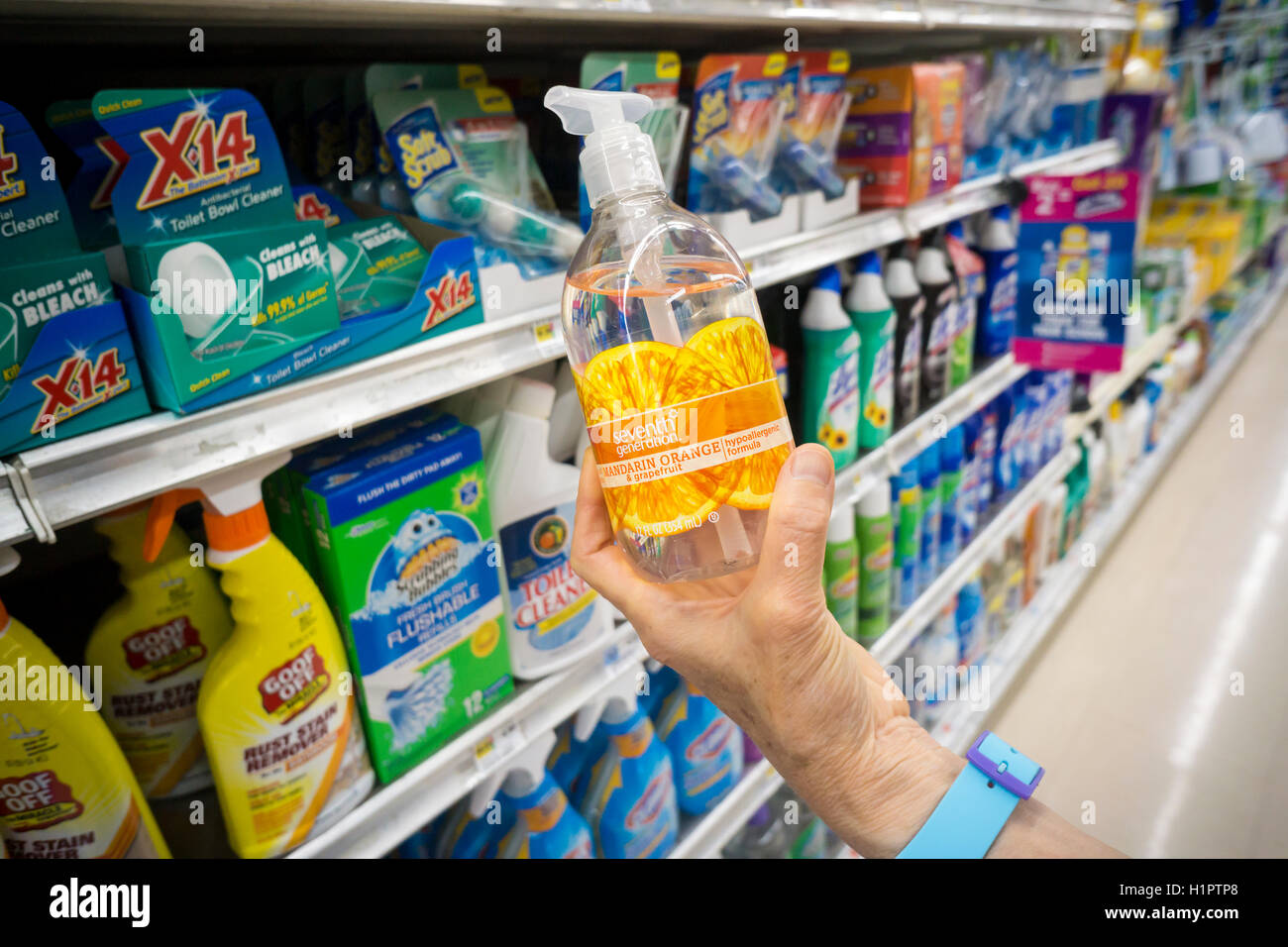 A shopper chooses a bottle of Seventh Generation brand disinfecting hand soap on a supermarket shelf in New York - Stock Image
