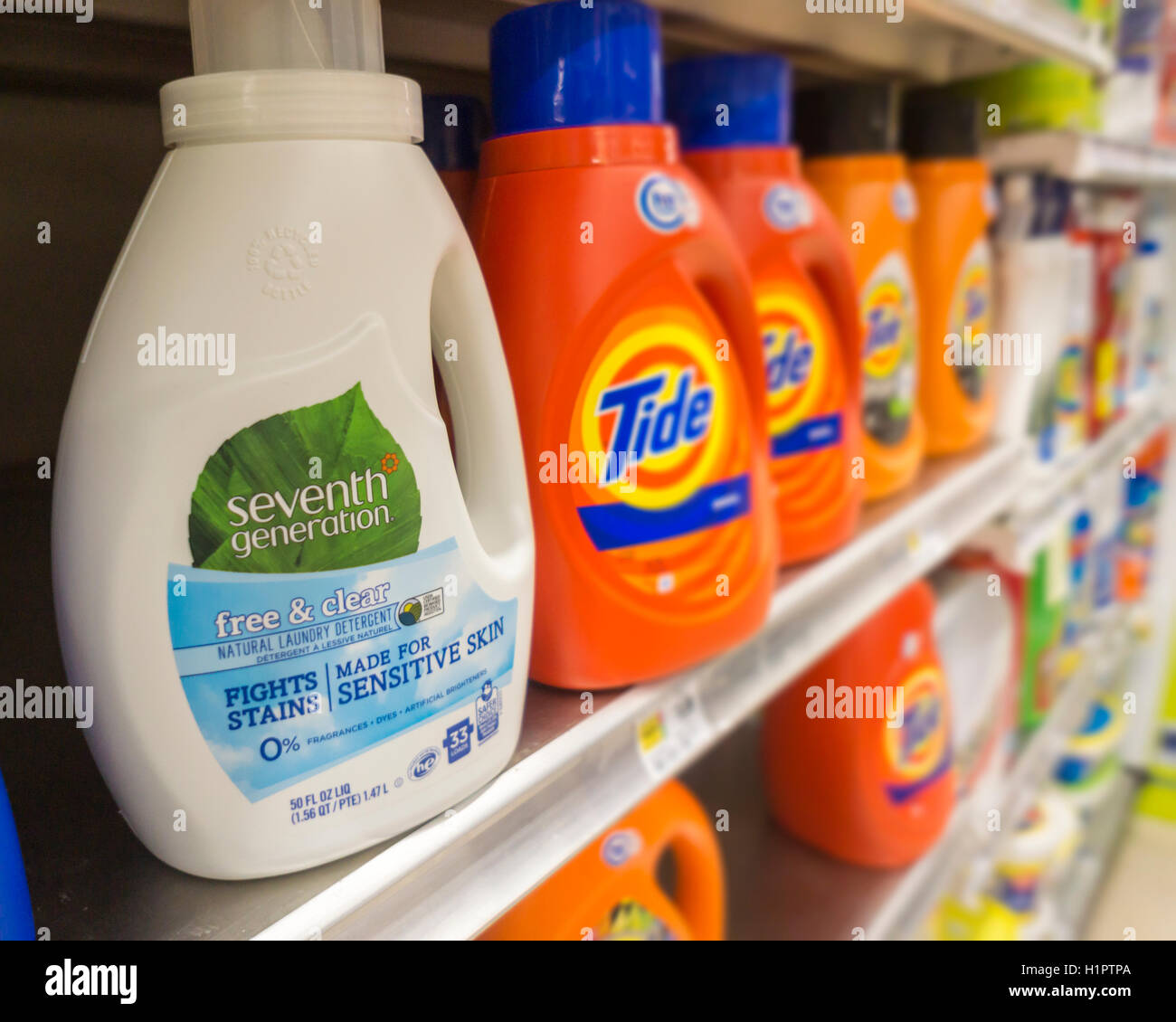 Seventh Generation brand laundry detergent next to market leader Procter and Gamble's Tide on a supermarket - Stock Image